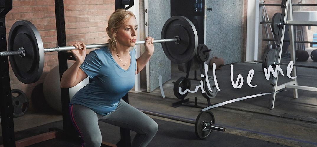 Confident woman lifting heavy weights in gym