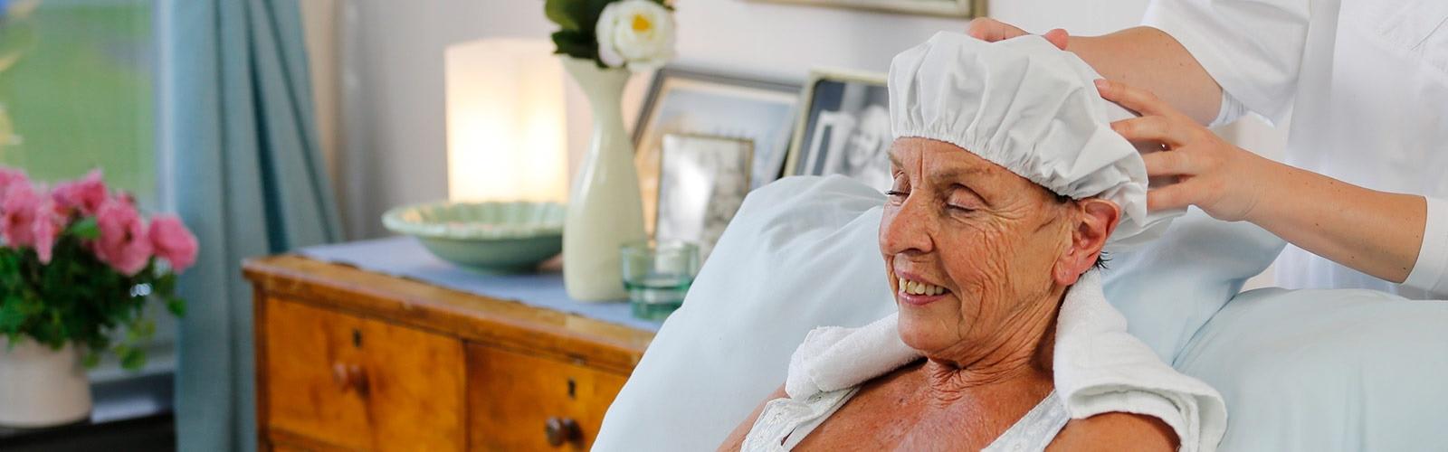 starší paní používající cepici na mytí vlasů TENA