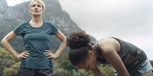 mature woman with blue tshirt exercising outdoors with younger woman