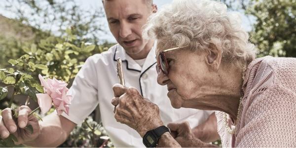 Äldre dam och manlig sköterska tittar på en ros