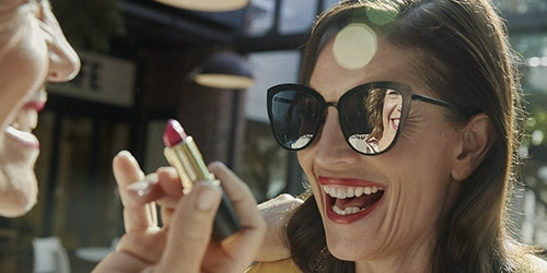 woman with sunglasses and lipstick laughing with friend outside