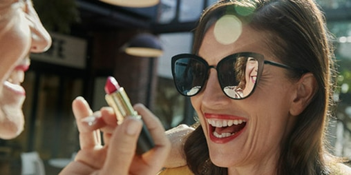 woman with sunglasses and red lipstick laughing with friend outside