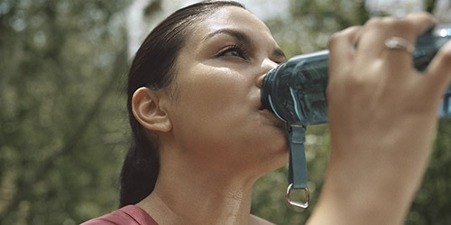 TENA-Women-Lifestyle-Woman-Drinking-Water-During-Hike