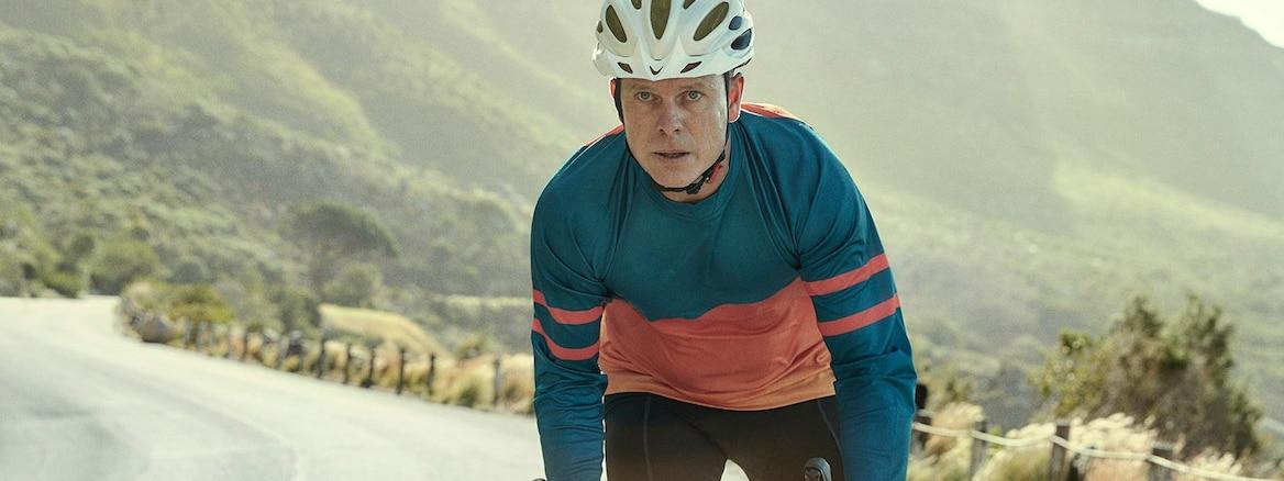 Mand, der cykler på en vej