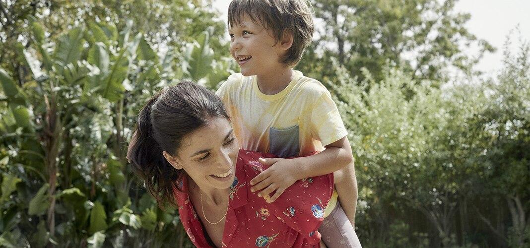 Junge Frau mit einem Kind auf dem Rücken.