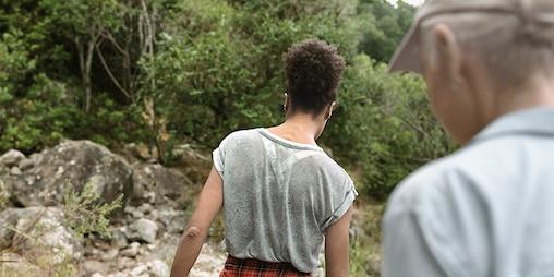 To veninder, der vandrer sammen, træer og klipper i baggrunden
