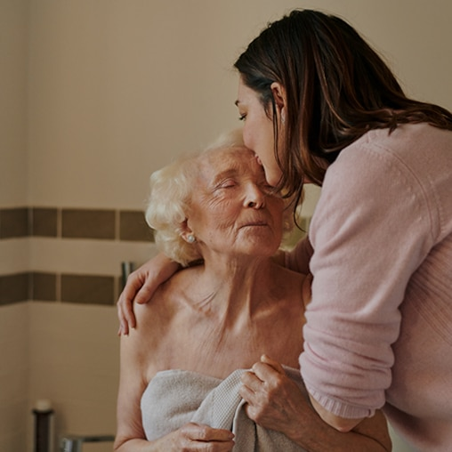 A woman gently kissing an elderly woman on the forehead.
