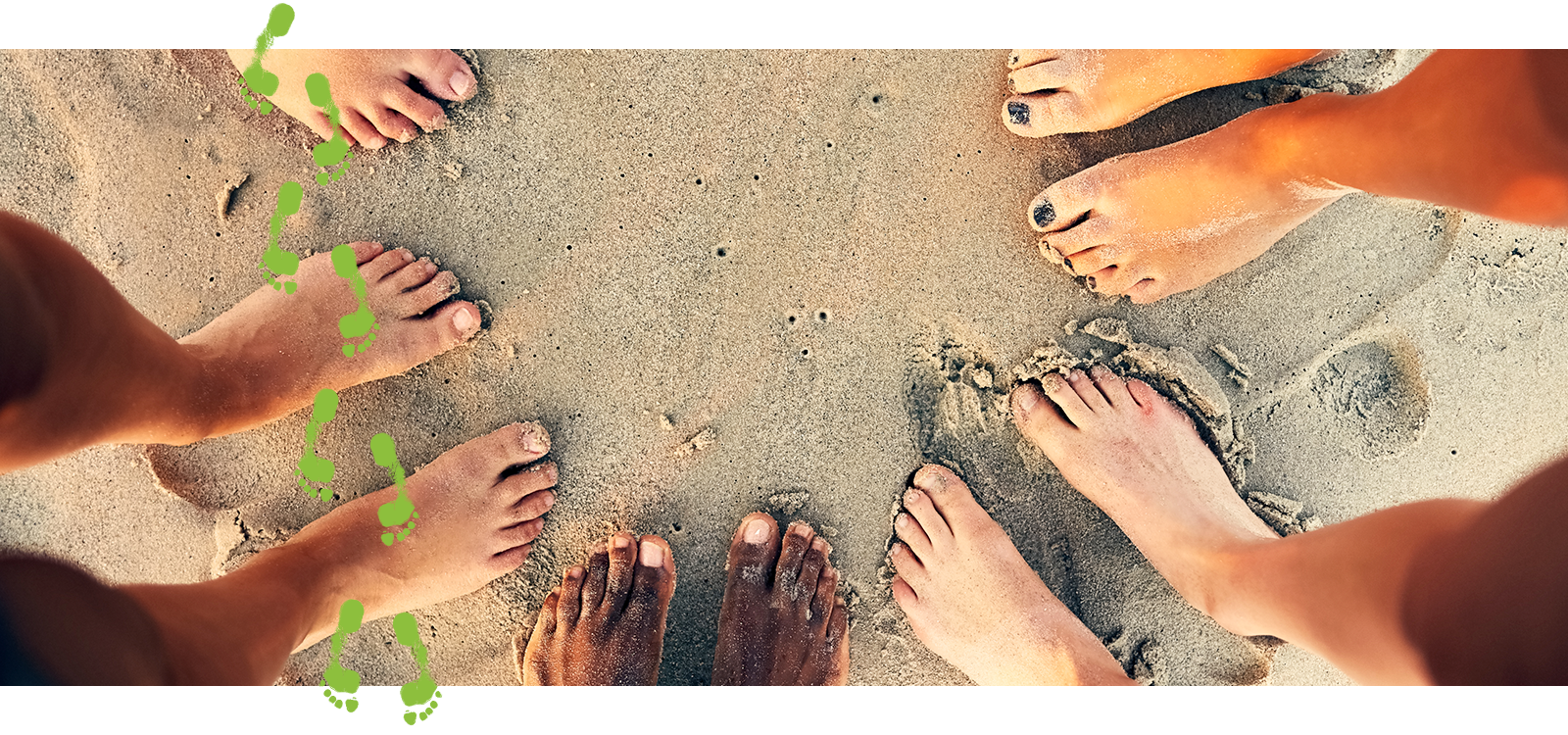 Bare feet of a group of people in a circle on a sandy beach