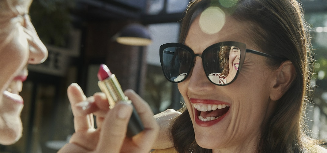 Woman applying lipstick using friends sunglasses as a mirror