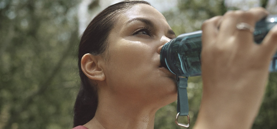 woman drinking water during hike