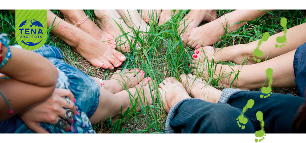 Bare feet of group of young girls in a circle on green grass