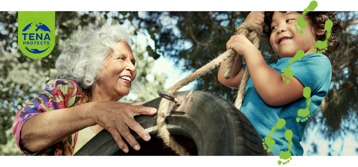 A smiling older woman pushes a young boy on a tire swing.