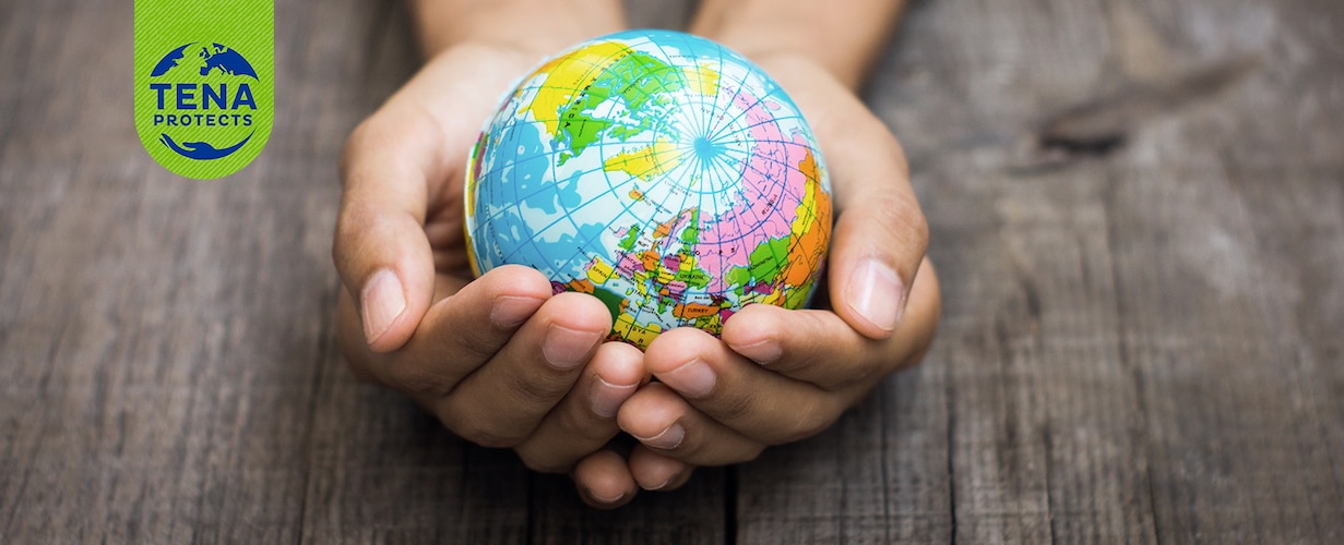Twee handen, rustend op een houten tafel, houden een kleine, kleurrijke wereldbol vast die het noordelijk halfrond laat zien.
