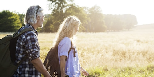 Άντρας και γυναίκα σε ώριμη ηλικία με σάκους που περπατούν σε ηλιόλουστο χωράφι