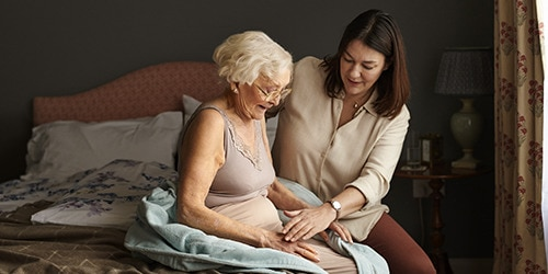 Carer helping older woman getting out of bed