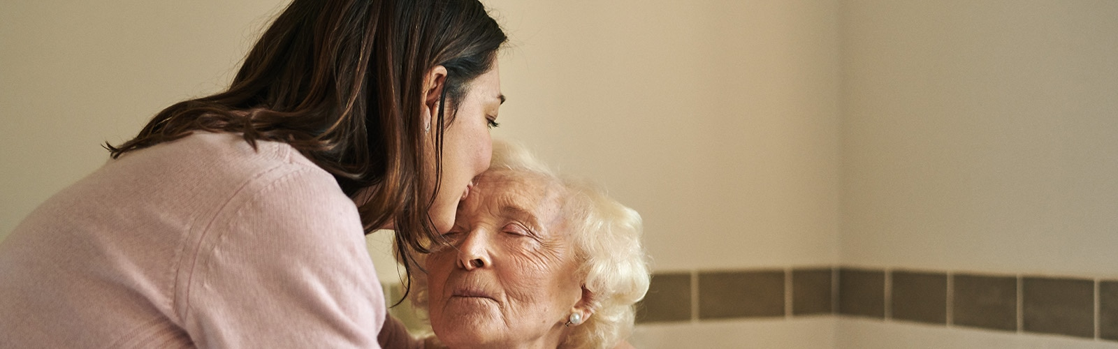 Carer kissing elderly woman with incontinence on the forehead
