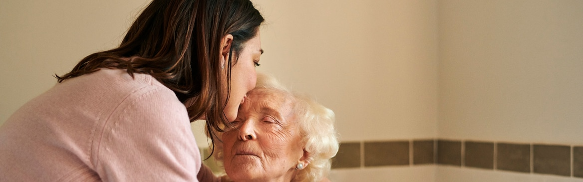 Elderly woman kissed by carer on the forehead