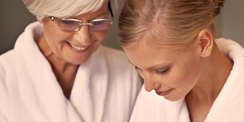Elderly woman taking care of her skin with younger woman