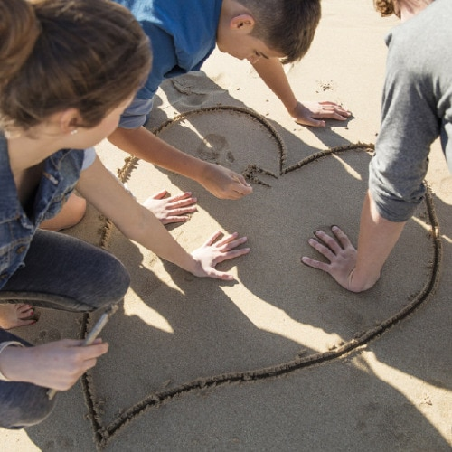 Three children on a beach write a message and make hand prints inside a heart they have drawn in the sand.