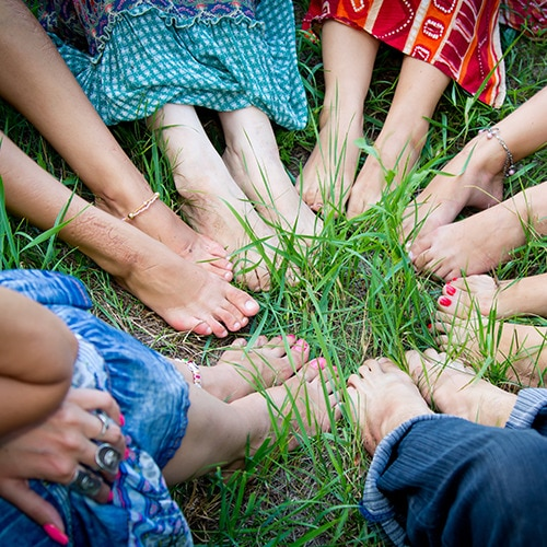 Seven pairs of feet form a circle in tall green grass.