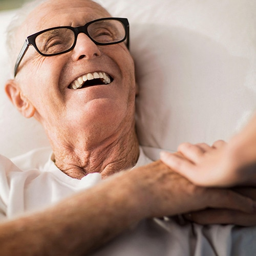 A smiling, elderly male resident wearing glasses lying in bed in a care home environment