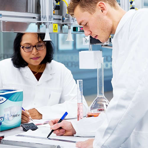 Two researchers in white scrubs consult their notes in a lab.