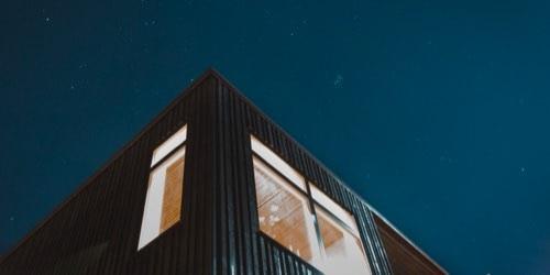 Pohľad spod rohu domu s jasnou nočnou oblohou s hviezdami hore