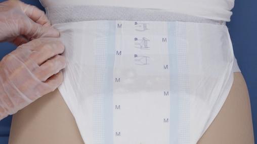 Кадр из видеоролика, в котором ухаживающий за близким помогает надеть подопечному, сохранившему частичную подвижность, подгузник TENA Flex.
