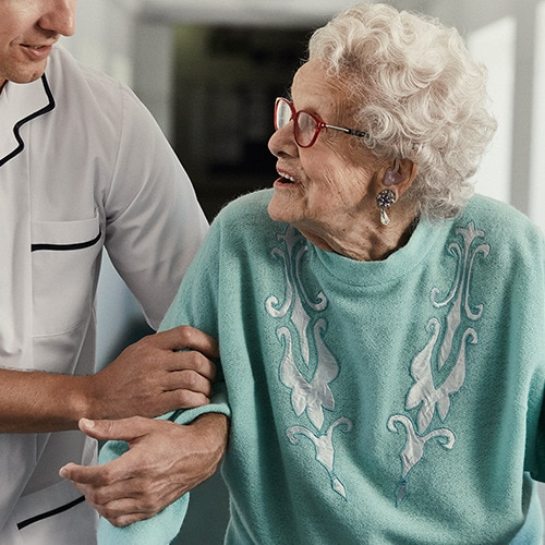 A professional caregiver supporting an elderly female resident while walking in a care home environment
