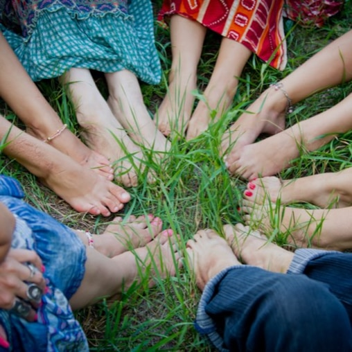 Bare feet of a group of young girls in a circle on green grass.