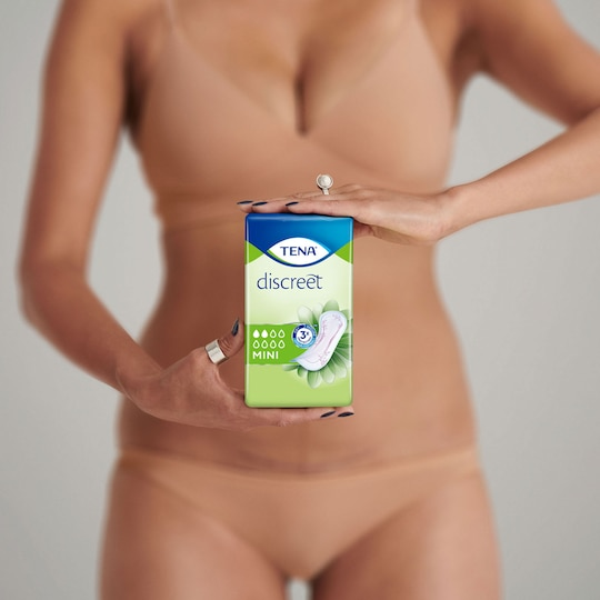 A woman holding a package of TENA Discreet Mini