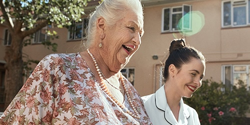 A smiling elderly female resident taking a walk outdoors with a professional caregiver