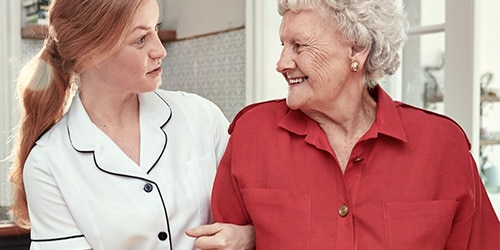 A female professional caregiver links arms and converses with an elderly female resident in a care home environment