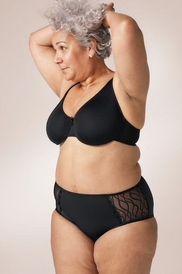 White woman wearing a black bra and a pair of TENA Silhouette Washable Absorbent Underwear in a Classic brief.