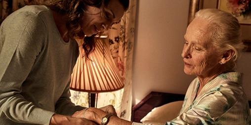 Yaşlı kadın yatağın üzerinde oturuyor