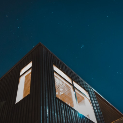 View from beneath of the corner of a house with a clear night sky with stars above