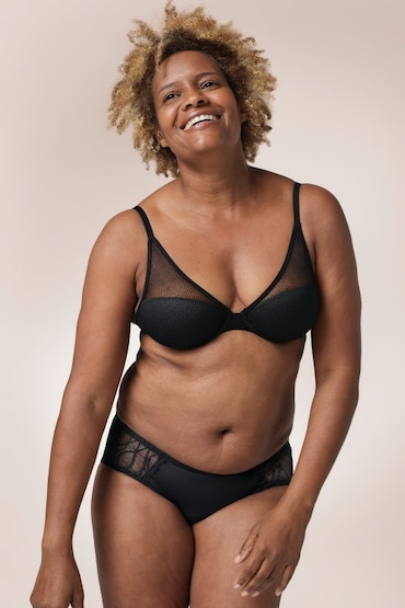 Black woman wearing a black bra and a pair of TENA Silhouette Washable Absorbent Underwear in a Hipster brief.