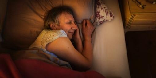 En ældre kvinde sover tungt i sin seng.