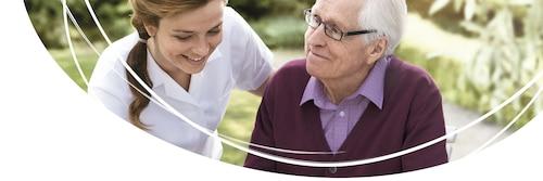 Mitarbeiter einer Pflegeeinrichtung im Gespräch mit einem Herrn