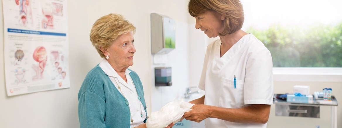 A doctor in her office shows an elderly patient how to use her new incontinence product.