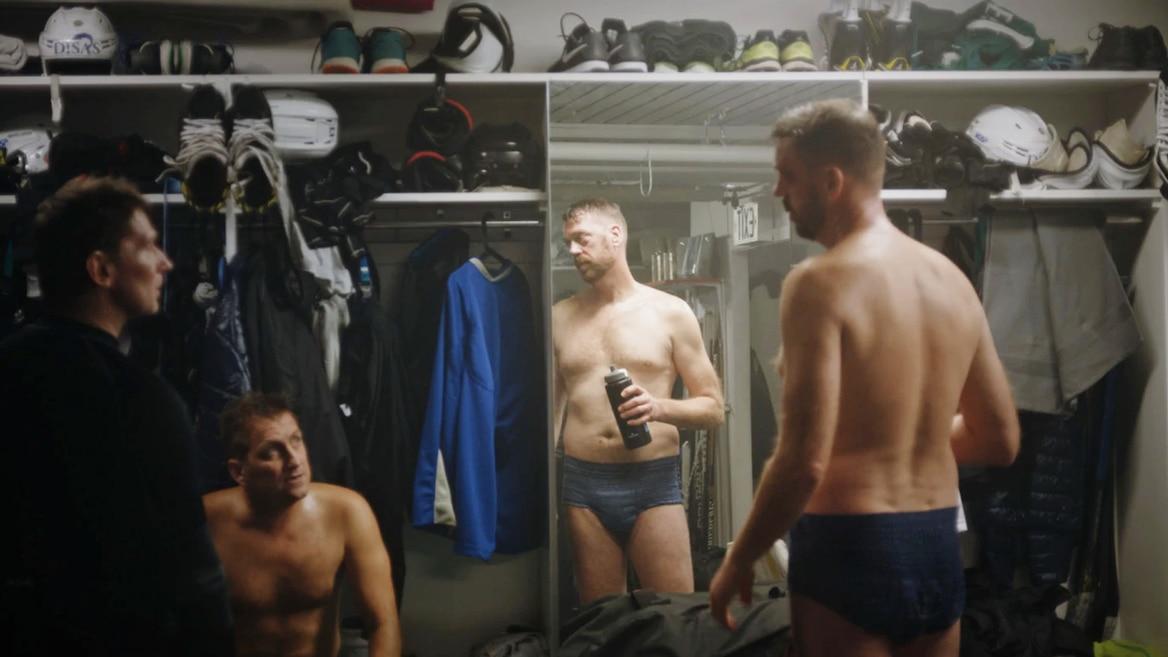 Men in locker room wearing TENA Men Active Fit Pants