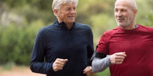 To midaldrende mænd, der jogger sammen udenfor.
