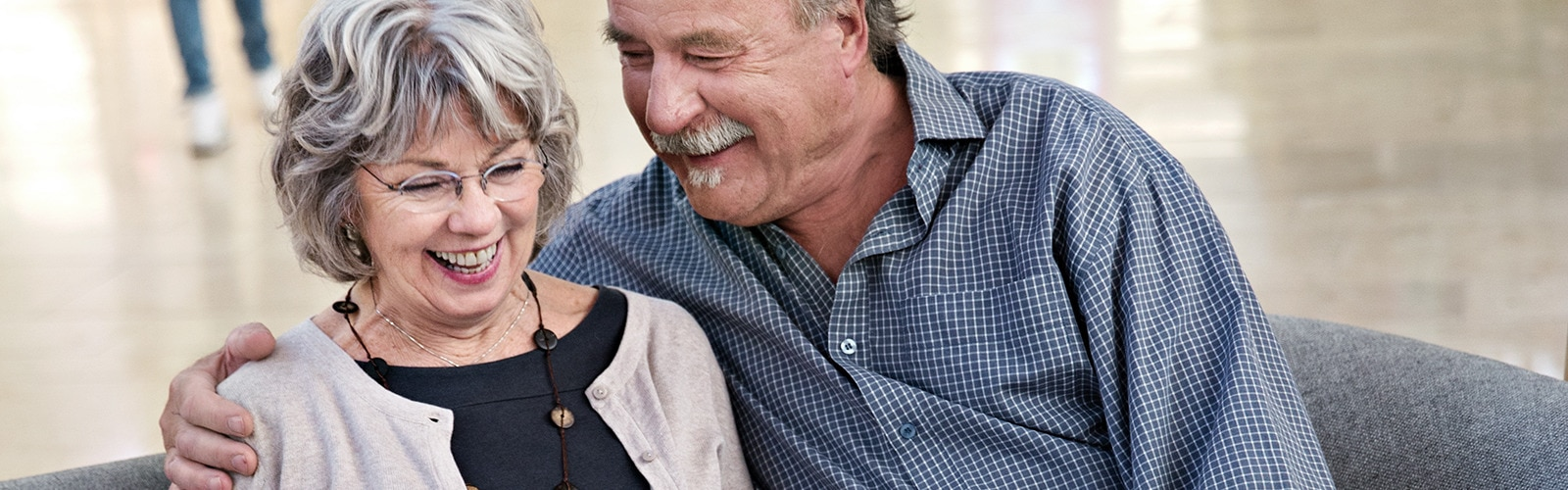 Ηλικιωμένο ζευγάρι που κάθεται στον καναπέ