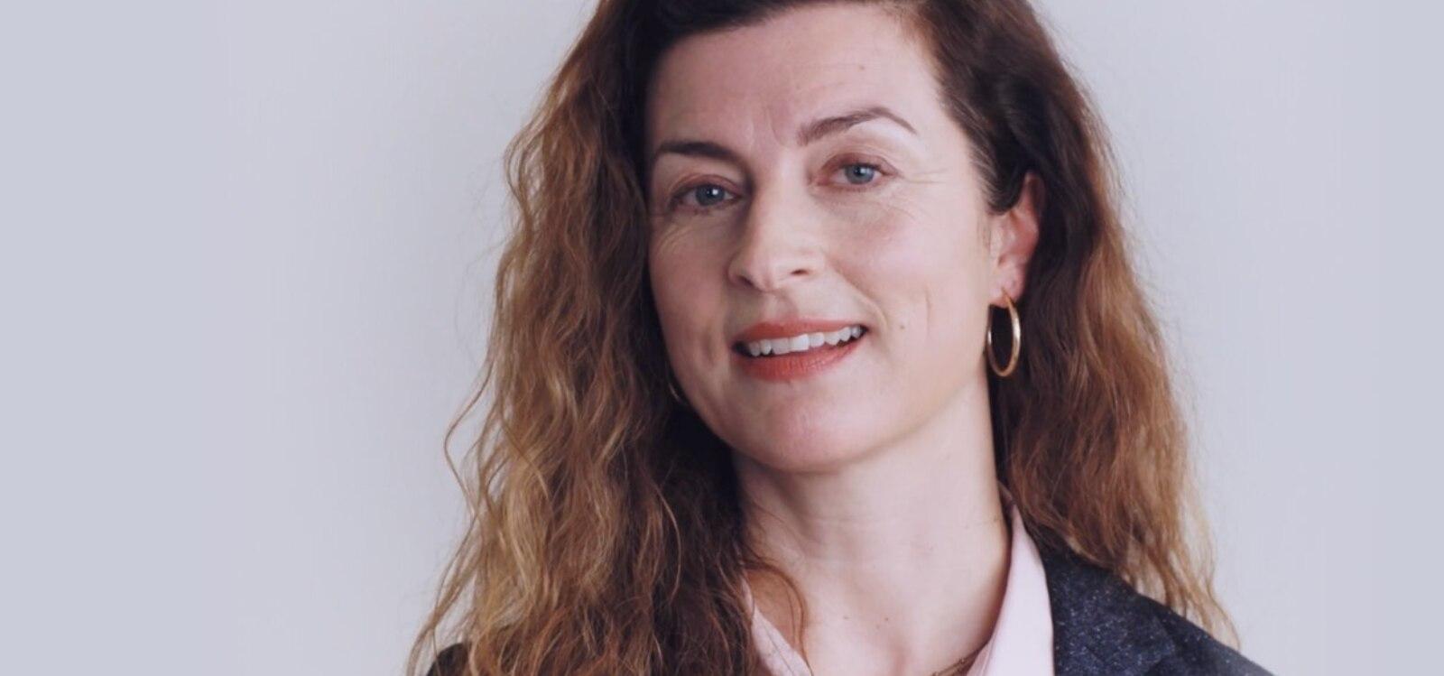Bild einer weißen Frau mit langem, braunem Haar, die lächelnd in die Kamera blickt. Grauer Hintergrund.
