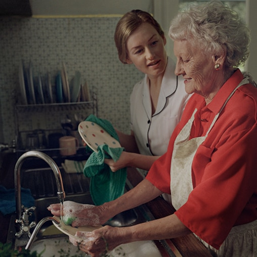 Nurse helping an elderly woman with her dishes.