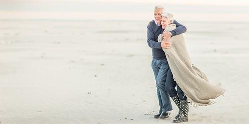 Vyresnio amžiaus vyras apsikabina žmoną, sušildydamas ją jiems vaikštant vėjuota pakrante