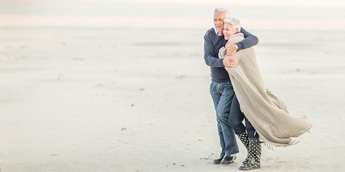 Un uomo anziano abbraccia sua moglie per tenerla al caldo mentre camminano su una spiaggia ventosa