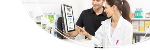 Apotheker, der einem Kunden am Computer hilft