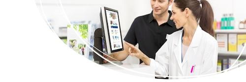 Lékárník před počítačem pomáhá zákazníkovi