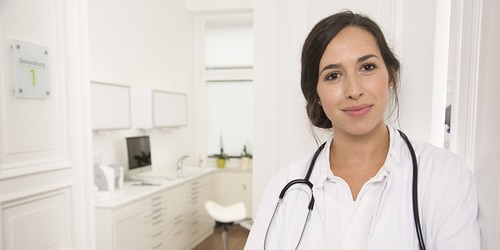 Naeratav arst praksise taustal
